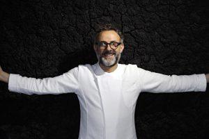 Fotografia di Massimo Bottura a braccia apertesu sfondo nero